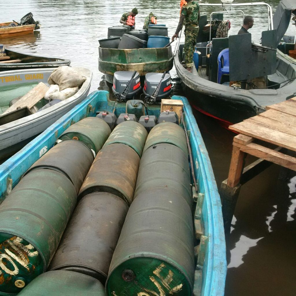 Outboard engines and drum for illegally refined oil seized by the troops