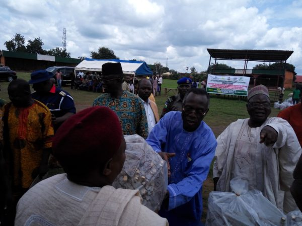 Chief Audu Ogbeh presenting cassava stem cuttings to a beneficiary. Chief John Anteni (right) points hand to stress a point.