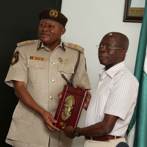 Governor Oshiomhole of Edo State presents a souvenir to Mr D.Y Adi, new Comptroller Immigration Service, Edo State