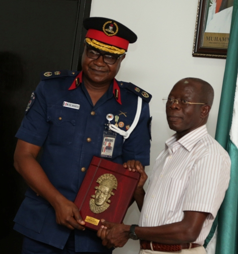 Governor Oshiomhole presents a souvenir to Dr Eze Benito, new Commandant Nigerian Security and Civil Defence Corps (NSCDC) Edo State during the visit