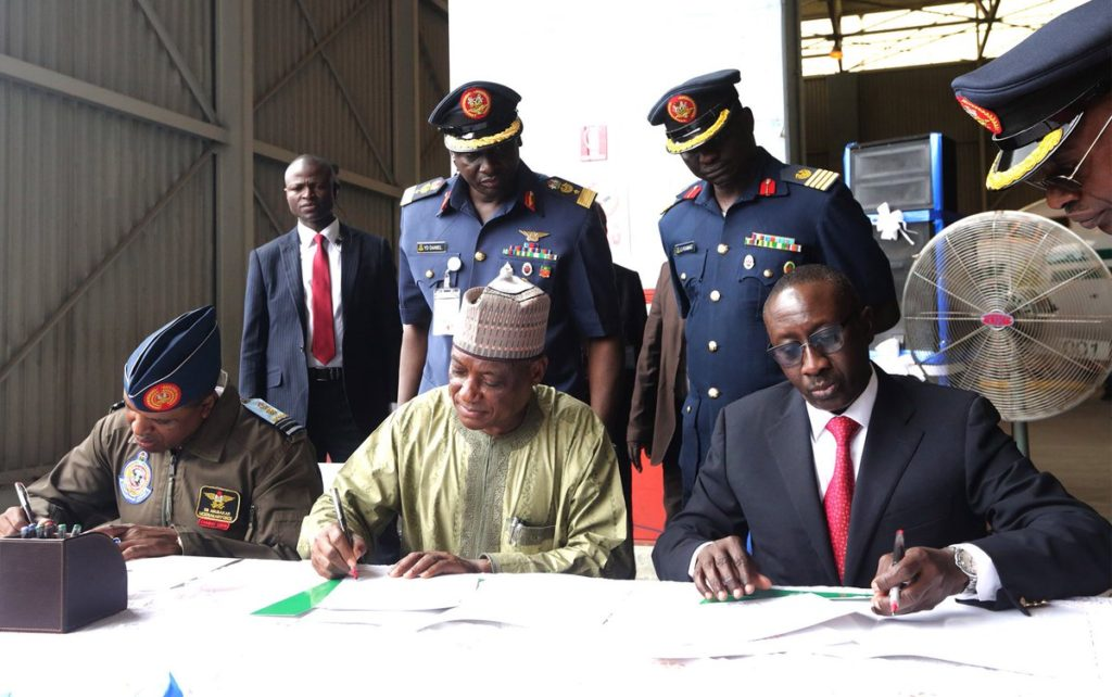 At the handover ceremony, Mansur Dan Ali, the Minister of Defence, Babagana Monguno, the National Security Adviser and Abubakar Sadique, the Chief of Air Staff append signature to the hand over agreement