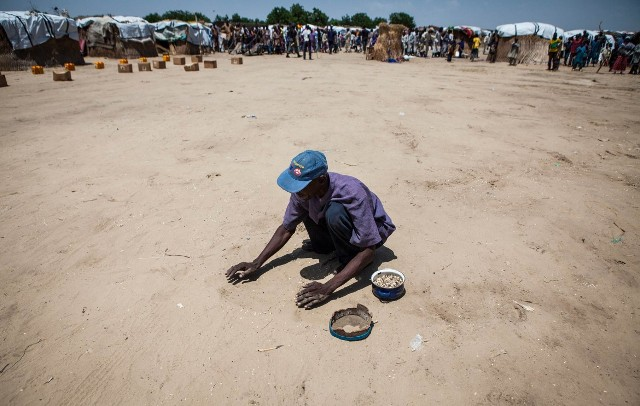 Hamadu Husseiny, 28, searches for beans that have fallen during food distribution at a camp in Monguno, Nigeria, on Sept. 27. As a result of government inaction and underestimates of the size of the disaster by U.N. and humanitarian groups, little aid has reached those in need in Borno state.