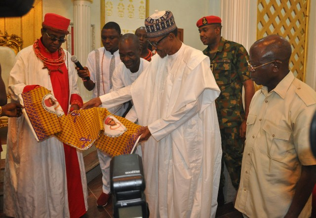 Oba of Benin, Oba Ewuare II, presents a gift to President Muhammadu Buhari, with them is Governor Adams Oshiomhole of Edo State, during the President's visit to him