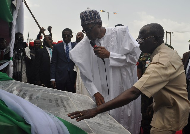 President Muhammadu Buhari unveils the plaque, assisted by Governor Adams Oshiomhole, at the commissioning of the 6-lane Upper Siluko road with street lights and walkways, in Benin City, on Monday