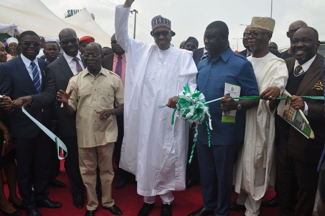President Muhammadu Buhari (middle) cuts the tape to commission the  6-lane Upper Siluko road with street lights and walkways, flanked by Governor Adams Oshiomhole (right), Prince Clem Agba, Commissioner for Environment (left); Chief John Odigie-Oyegun, APC National Chairman, (2nd left) and Rt Hon Justin Okonoboh (3rd left); Mr Godwin Obaseki, Governor-elect (2nd right) and Hon Philip Shaibu, Deputy Governor-elect (3rd right)
