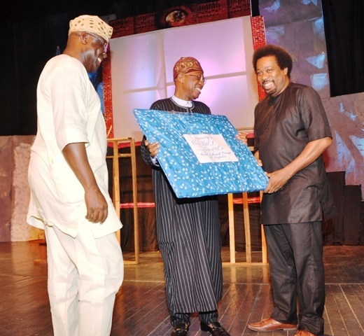 """Minister of Information and Culture Lai Mohammed (Middle) receiving a souvenir from Makin Soyinka during the Command Performance of ''Death and the King's Horseman"""" in Lagos on Saturday to commemorate the 30th anniversary of the award of Nobel Prize to Prof. Wole Soyinka. Artistic Director of the National Troupe, Akin Adejuwon (left) looks on."""