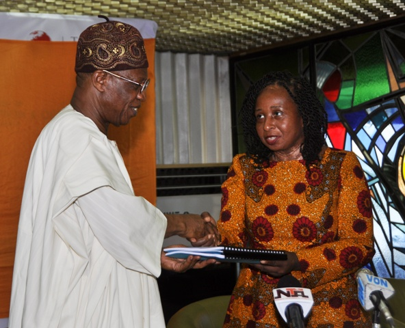 Mohammed receiving the document from Chairperson of the Committee, Ms Peace Anyiam-Osigwe,