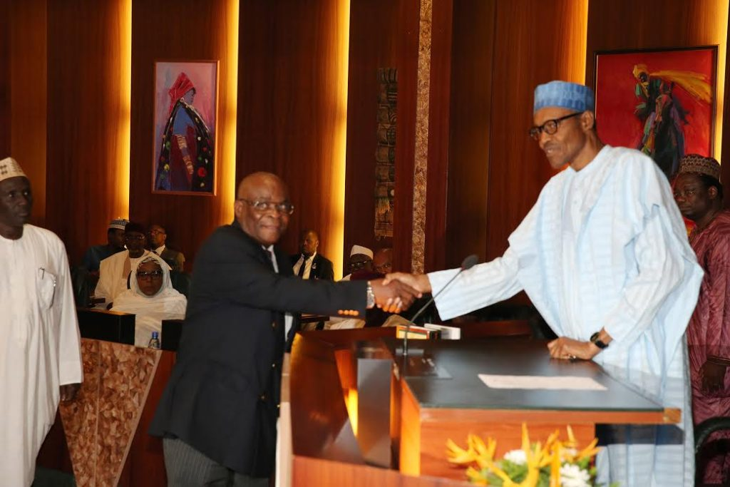 President Buhari shakes Justice Walter Onnoghen after swearing him in as the Acting Chief Justice of Nigeria (CJN).
