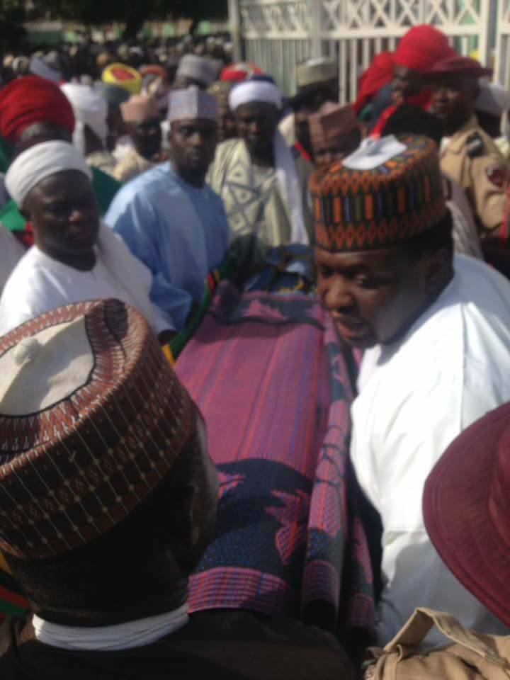 Rep. Abdussamad Dasuki, right, in white dress joined in carrying the remains of his father for burial