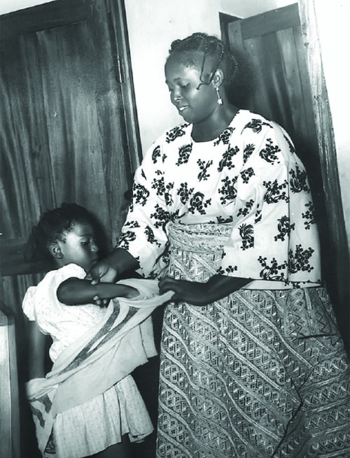 """Hannah helping the """"baby of the family"""" Tokunbo, to remove her jumper in the early 1950s"""