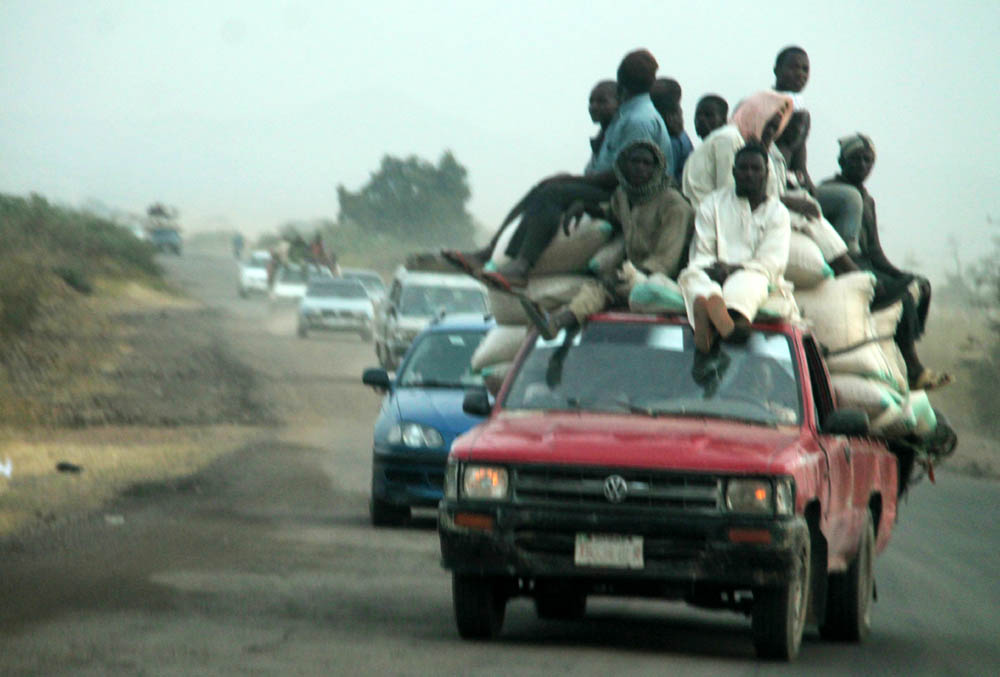 Perching dangerously: Passengers on top of this truck captured on Numan-Adamawa highway were not bothered about the possibility of falling off the vehicle