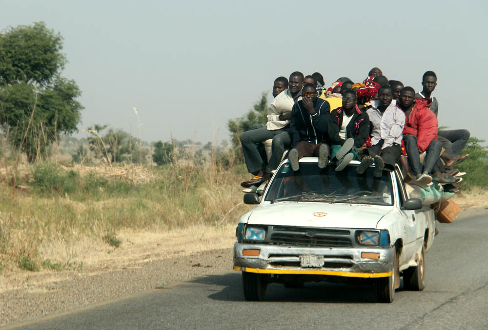 Loaded to the hilt: Passengers on top of this vehicle captured on Numan-Adamawa Highway seem not bothered that their legs are obstructing the view of the driver