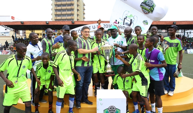 L-R: Chief Executive Officer, Etisalat Nigeria, Matthew Willsher; Captain of Asegun Comprehensive High School U-15 School Team, Ajibade Kehinde and President, Nigerian School Sports Federation (NSSF), Mallam Ibrahim Muhammad with the victorious players and coaching crew during the presentation of the Champions Trophy won by the school at the Etisalat U-15 School Cup Final held at the Campos Mini-Stadium, Lagos on Saturday.