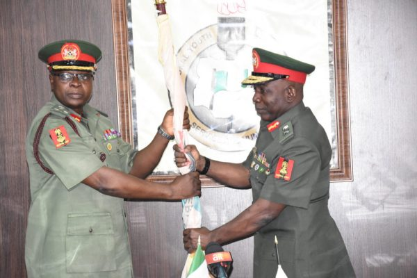 Former NYSC Director-General, Maj.-Gen. Suleiman Kazaure (Right) hands over NYSC Flag to Newly Appointed NYSC Director-General, Brig.-Gen. Shuaibu Ibrahim (Left) as he officially assumes office