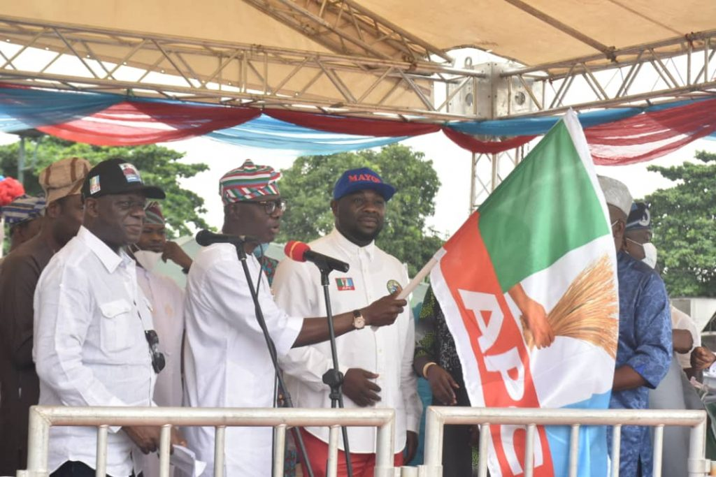 Governor Babajide Sanwo-Olu handing over flags to Lagos APC chairmanship candidates at the official presentation of party's flags ahead of the July 24 Local Government election in Lagos.