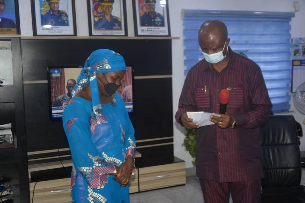 The Secretary to the State Government, Dr. Tammy Wenike Danagogo handing over cheques to one of the widows.