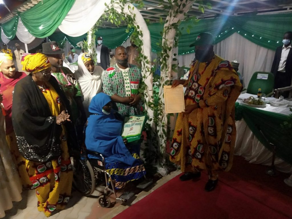 Governor Ganduje presenting a letter of permanent and pensionable appointment to Khadijah Umar who lost her legs in the course of her service to Kano state