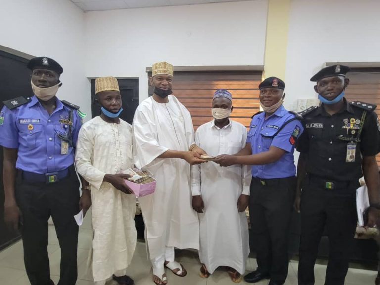 Kano Commissioner of Police, Mr Sama'ila Dikko, handing over the money to the relatives of the deceased