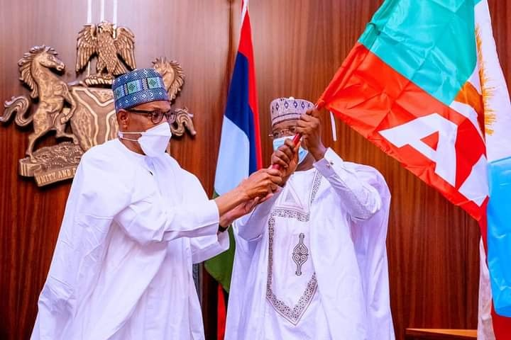Governor Matawalle receiving APC flag from President Buhari when he defected to the party