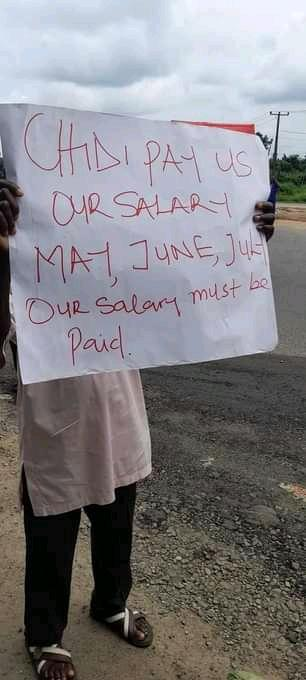 One of the workers with his placard protesting over the unpaid salaries