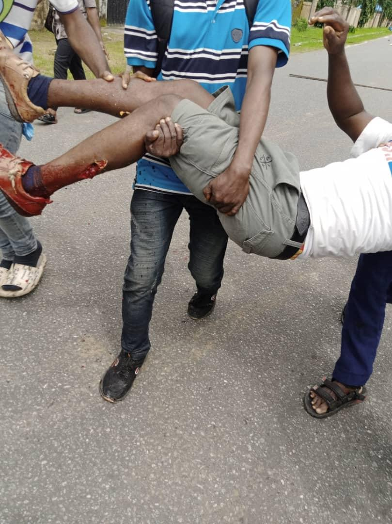 Some protesting Julius Berger workers rescuing an injured Colleague allegedly shot by Police in Bori, Khana Local Govt.