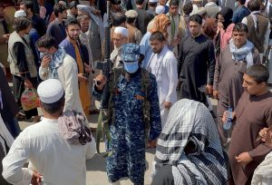 A member of Taliban security forces stands guard among crowds of people walking past in a street in Kabul, Afghanistan September 4, 2021. REUTERS/Stringer.